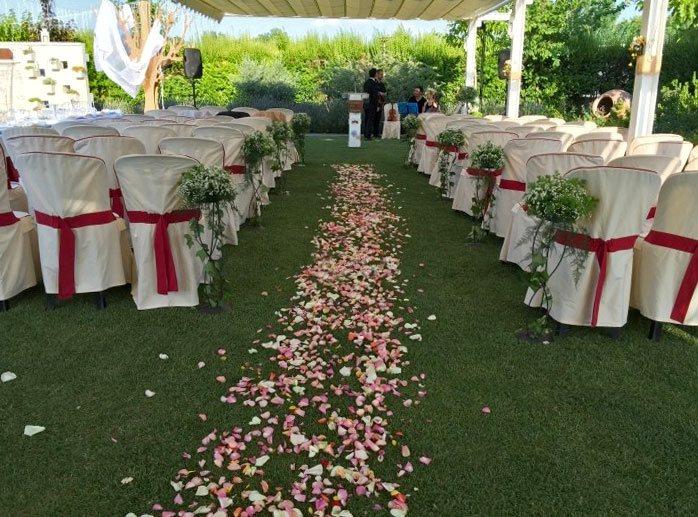 celebración de boda en un jardín con pétalos en el suelo