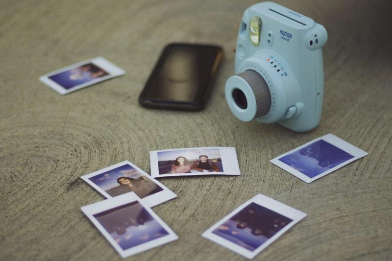 fotos polaroid con cámara fujifilm sobre una mesa de madera